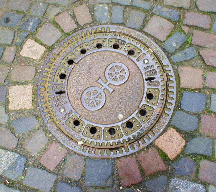 """Gullideckel mit """"Mainzer Rad"""", Wappen der Stadt Mainz."""